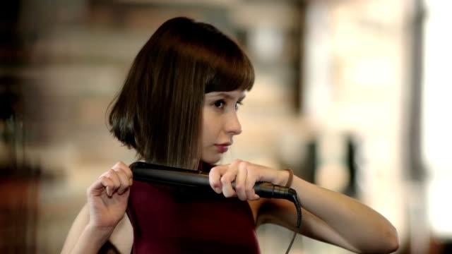 güzel ve genç birbayan demir saç düzleştirme - ayarlamak stok videoları ve detay görüntü çekimi