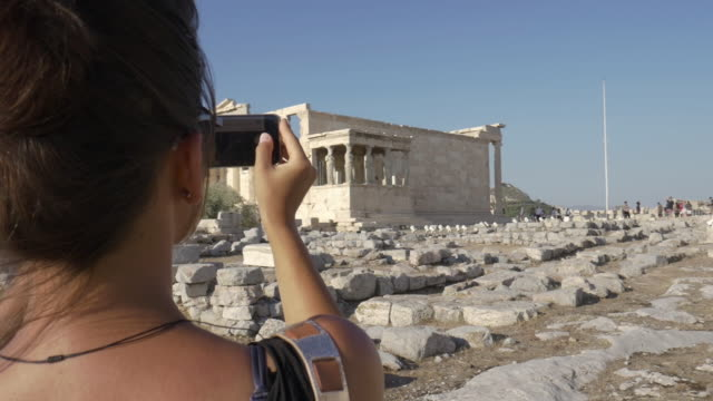 Beautiful young woman taking pictures at Parthenon in Athens Greece with smartphone camera video