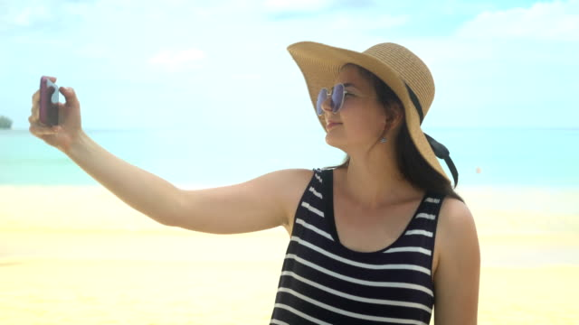 beautiful young woman taking selfie on beach
