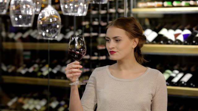 Beautiful young woman tasting red wine video