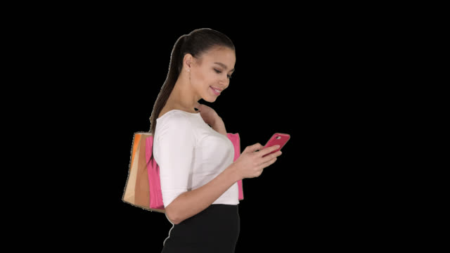 Beautiful young woman using a mobile phone walking and holding shopping bags, Alpha Channel