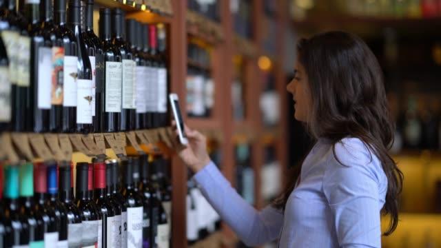 아름 다운 젊은 여 자가 그녀의 스마트폰에서 와인 응용 프로그램 사용 하 여 와인의 속성 - 와인병 스톡 비디오 및 b-롤 화면