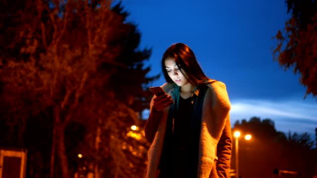 schöne junge frau mit ihrem smartphone zu fuß - schwarzes haar stock-videos und b-roll-filmmaterial