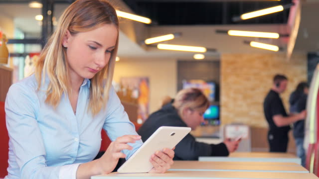 beautiful young woman using ipad tablet touch screen in cafe video