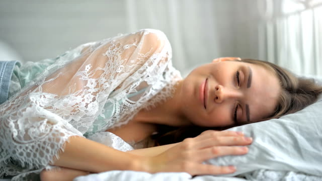 Beautiful young woman waking up in the light white room video
