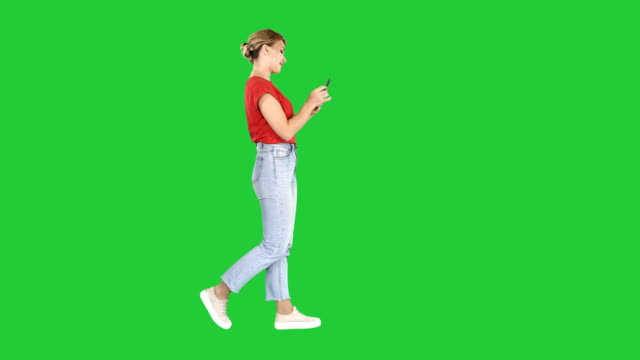 Beautiful young woman walking and reading text message on her mobile phone on a Green Screen, Chroma Key Full length shot. Side view. Beautiful young woman walking and reading text message on her mobile phone on a Green Screen, Chroma Key. Professional shot in 4K resolution. 006. You can use it e.g. in your commercial video, business, presentation, broadcast full length stock videos & royalty-free footage