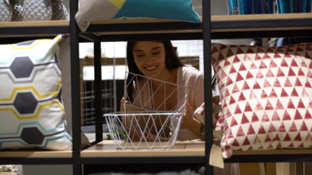 beautiful young woman walking at a furniture store and grabbing a basket from the retail display - dekoracja filmów i materiałów b-roll