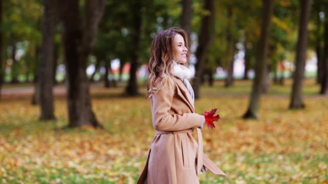vídeos y material grabado en eventos de stock de bella mujer caminando en el parque otoño - abrigo