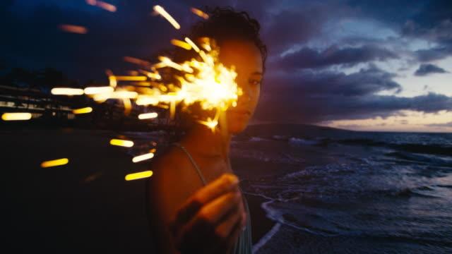 vidéos et rushes de belle jeune femme marchant avec feux d'artifice de cierge magique sur la plage au crépuscule - mode de la plage
