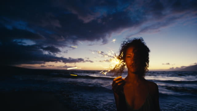 Beautiful young woman walking with sparkler fireworks on the beach at twilight
