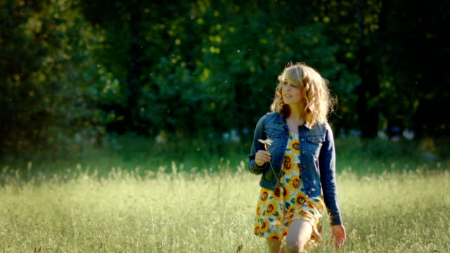 Beautiful Young Woman Walks Through Field, She Looks Around, And Smells A Flower video