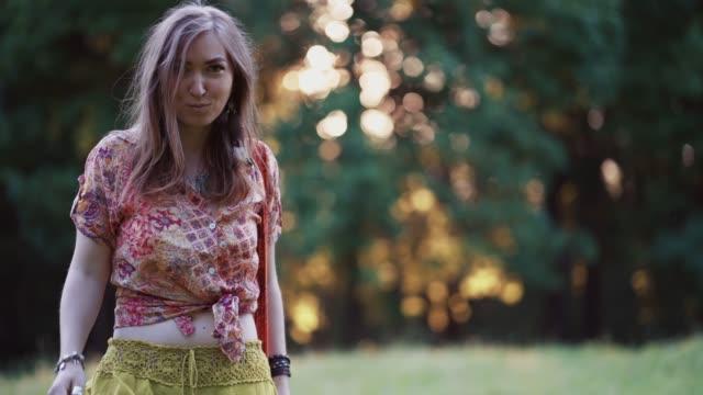 vídeos de stock, filmes e b-roll de linda jovem vestindo roupas bohostyle posando nos raios do sol da noite, pôr do sol. moda estilo boho, mulher vestindo joias prateadas se divertindo em parque ao ar livre - boho