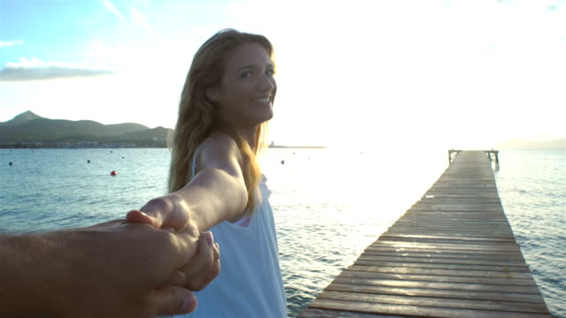 Beautiful young woman wearing white dress holding hand and leading her friend on pier video