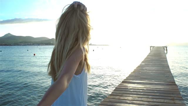 beautiful young woman wearing white dress holding hand and leading her friend on pier - podążać za czynność ruchowa filmów i materiałów b-roll