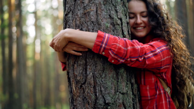 Beautiful young woman with curly hair wearing bright shirt is hugging tree enjoying nature and smiling with closed eyes. People, recreation and happiness concept.