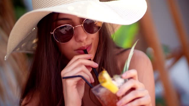 Beautiful young woman with hat, sunglasses and cocktail in summer
