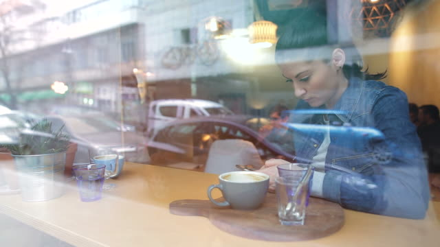 bellissima giovane donna con il suo smartphone. - caffetteria video stock e b–roll