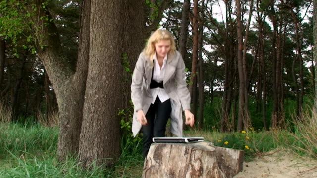 Bella mujer joven con ordenador portátil en el bosque - vídeo
