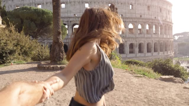 Beautiful young woman with long hair lead boyfriend by the hand towards colosseum in rome at sunset come with me attractive happy couple Beautiful young woman with long hair lead boyfriend by the hand towards colosseum in rome at sunset come with me attractive happy couple girlfriend stock videos & royalty-free footage
