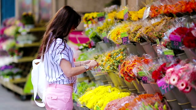 Beautiful young woman with long hair selecting fresh flowers at european market video