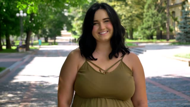 vídeos de stock e filmes b-roll de beautiful young woman with obesity smiling and looking at camera, standing on street in park, charming and happy - corpulento