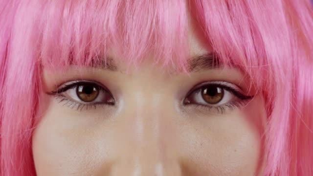 stockvideo's en b-roll-footage met mooie jonge vrouw met roze haar kijkt naar de camera. - roze haar