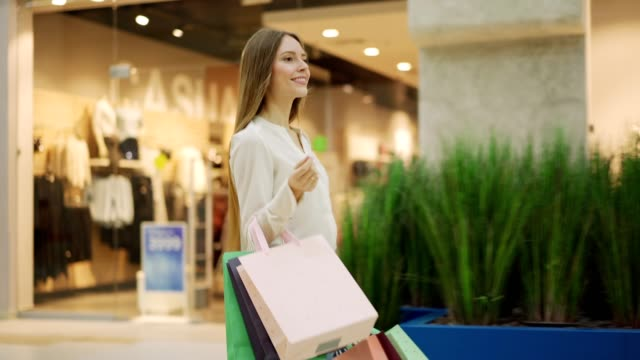 vídeos de stock e filmes b-roll de beautiful young woman with shopping bags walking along mall, looking at window displays and smiling after successful shopping, three quarter length tracking shot - centro comercial
