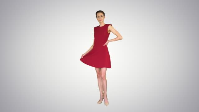 schöne junge frau mit kurzen haaren im roten kleid posiert auf gradienthintergrund - ganzkörperansicht stock-videos und b-roll-filmmaterial