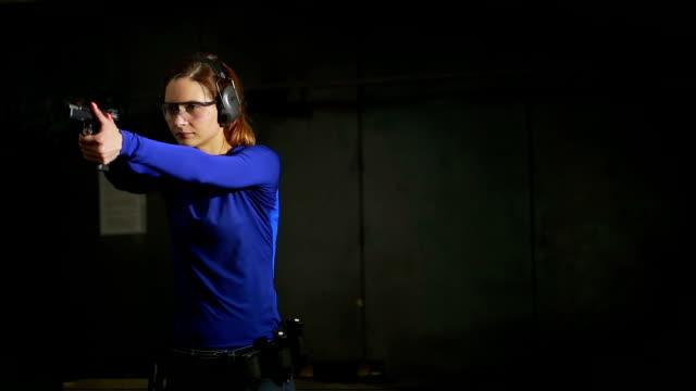 beautiful young woman with the gun on an indoor shooting range. shoots a gun - огнестрельное оружие стоковые видео и кадры b-roll
