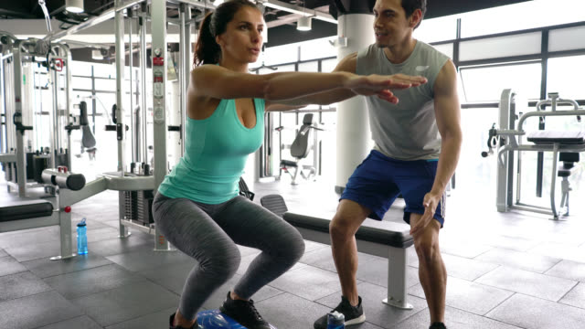 beautiful young woman working out on balance half ball and personal coach standing next to her - allenatore video stock e b–roll