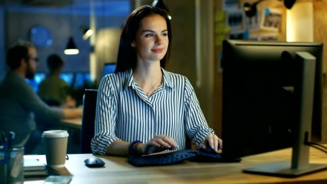 Belle jeune femme travaille sur ordinateur personnel, elle sourit délicieusement dans la caméra. Elle travaille dans un Studio moderne bureaux Loft. - Vidéo