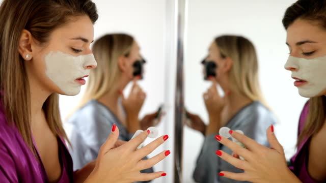 Beautiful young women applying facial mask