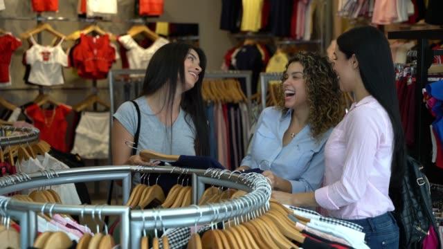vídeos de stock, filmes e b-roll de mulheres bonitas em uma loja de roupa olhando para escolhas diferentes ao mesmo tempo rindo - boutique