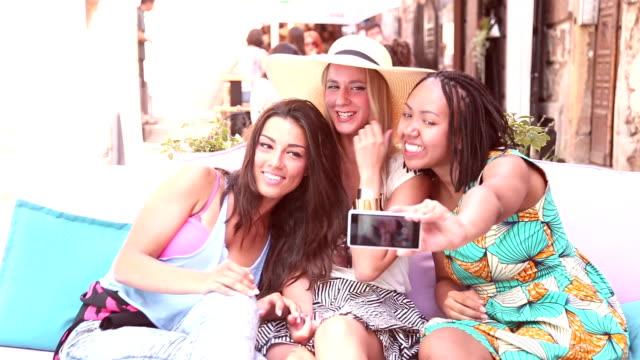 Beautiful young women having fun taking selfies in town video