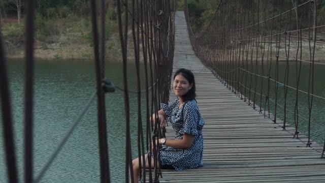 Beautiful Young Women Sitting on Bridge