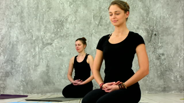 beautiful young women working out in loft interior, doing yoga exercise, sitting in easy asana for meditation, mudra hand gesture - mindfulness stock videos & royalty-free footage