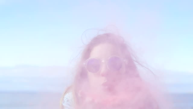 vídeos de stock e filmes b-roll de beautiful young young girl with brown hair and in cool sunglasses blows holi colorful powder off her hands and laughs. clear blue sky behind her. - holi