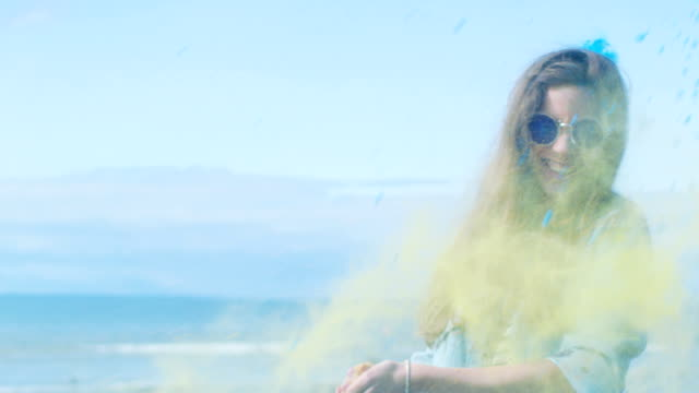 vídeos de stock e filmes b-roll de beautiful young young girl with brown hair  wearing cool sunglasses is hit by a colorful holi powder, throws some in return and laughs. people celebrate holi festival. clear blue sky behind her and deep blue sea behind her. - holi