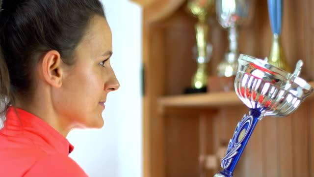 beautifull young woman puts the trophy on the shelf. sportswoman recived award. - campionato video stock e b–roll