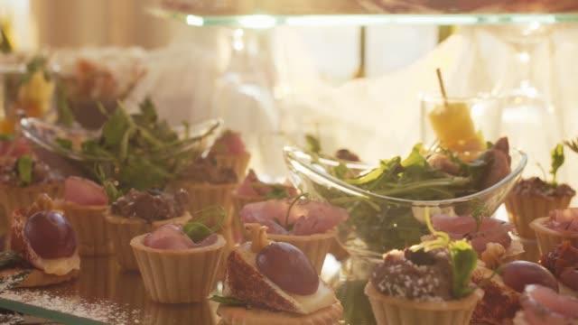 şirket noel doğum günü partisi olay ya da düğün kutlama güneşte farklı gıda aperatifler ve meze ile güzel dekore catering ziyafet masası. - ordövr stok videoları ve detay görüntü çekimi