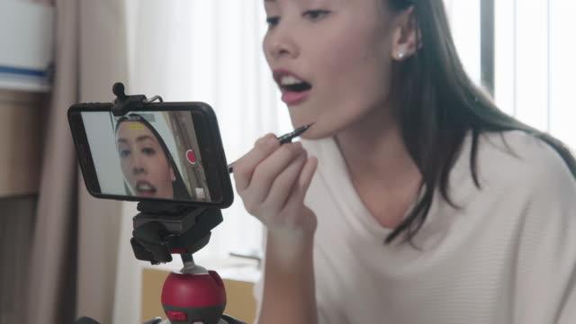 beauty-blogger, die zeigen, wie man produkte auf live-übertragung mit smartphone, leben eines influencer zu machen und zu überprüfen - bloggen stock-videos und b-roll-filmmaterial