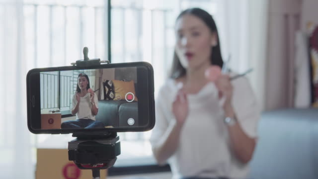 beauty blogger demonstrating how to make up and review products on live broadcast use smartphone, life of an influencer - influencer filmów i materiałów b-roll