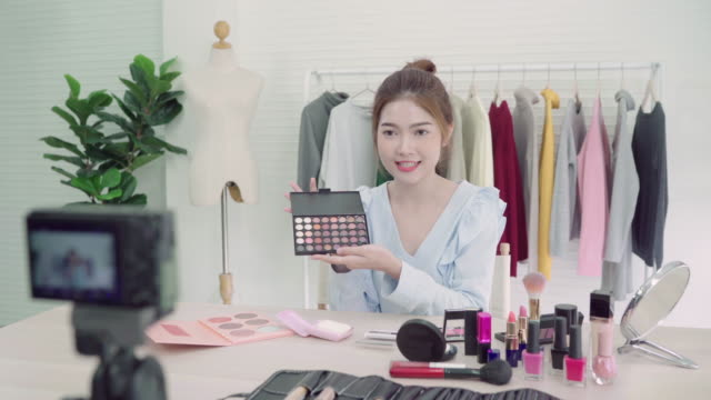 Beauty blogger present beauty cosmetics sitting in front camera for recording video. Beautiful asian woman use cosmetics while review make up tutorial broadcast live video to social network by internet.