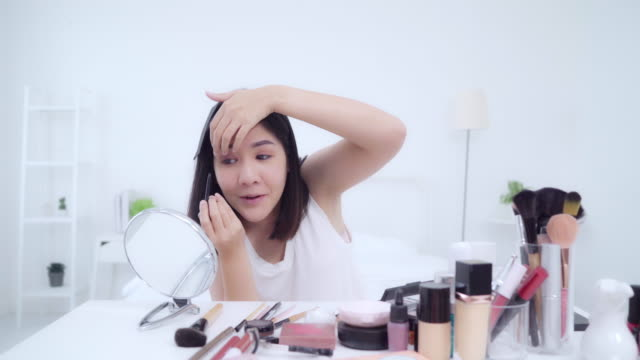 Beauty blogger present beauty cosmetics sitting in front camera for recording video. Happy beautiful young Asian woman use cosmetics review make up tutorial broadcast live video to social network.