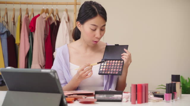 Beauty blogger present beauty cosmetics sitting in front tablet for recording video. Happy beautiful young Asian woman use cosmetics review make up tutorial broadcast live video to social network.