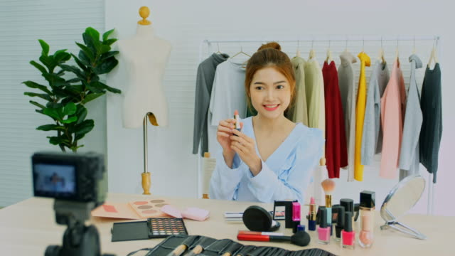 Beauty blogger, vlog showing cosmetics sitting in fornt of camera while recording video, Happy beautiful young asian woman influencer broadcast how to make  to social network