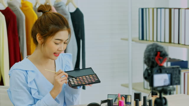 Beauty blogger, vlog showing cosmetics sitting in front of camera while recording video, Happy beautiful young asian woman influencer broadcast how to make  to social network