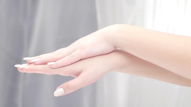 schönheitspflege. junge schöne frau anwendung feuchtigkeitscreme - fingernagel stock-videos und b-roll-filmmaterial