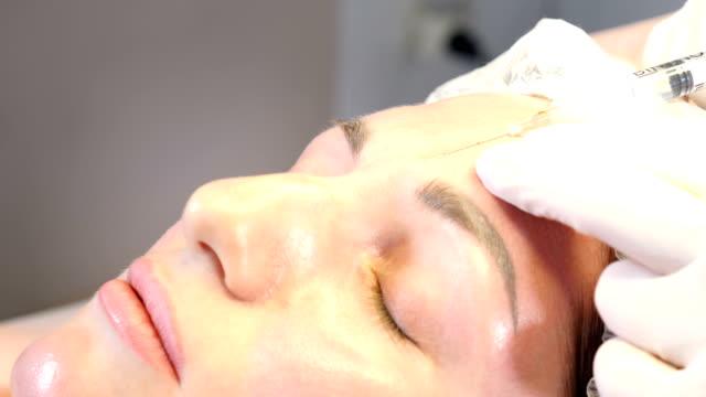 skönhetsklinik. kosmetolog händer i handskar gör ansikte åldrande injektion till kvinnlig hud. en kvinna får skönhet ansikts kosmetika förfarande. botox. kollagen injektioner. skjuten i 4k - acupuncture bildbanksvideor och videomaterial från bakom kulisserna