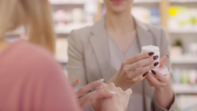 beauty consultant empfiehlt dem kunden handcreme - kosmetik beratung stock-videos und b-roll-filmmaterial